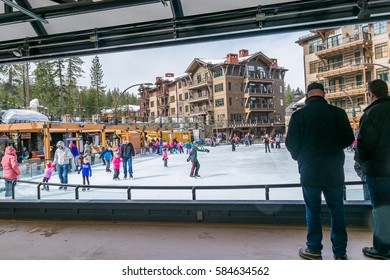 Truckee, California - February 19, 2017: Visitors and families ice skate at Northstar Village, near Lake Tahoe, as two men watch on the side. Hotel style lodging buildings are seen in the background.