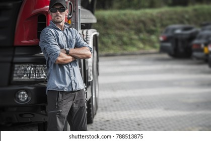 Trucker and His Semi Truck. Caucasian Driver in His 30s in the Delivery Hub. Transportation Theme.