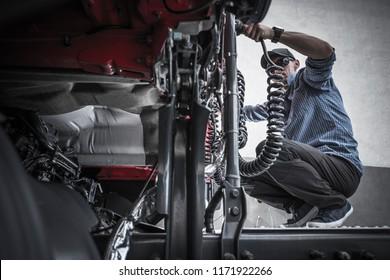 Trucker Semi Maintenance. Preparing Tractor Truck For the Next Trip. Caucasian Driver in His 30s.