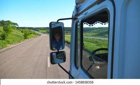 Trucker in sunglasses reflecting in side mirror of moving car. Man driving lorry riding to destination through countryside road. Cargo transportation concept. Beautiful background. Slow mo Close up