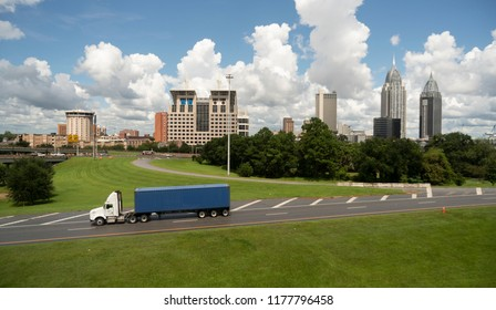A trucking shipping container matches the sky behind the downtown Mobile Alabama city skyline.