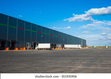 Trucks at big industrial warehouse building