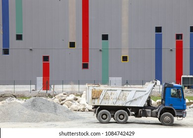 Trucks for construction site. Concrete, cement and building materials. Industrial area. Background of a shed made of sheet iron with colored strips.