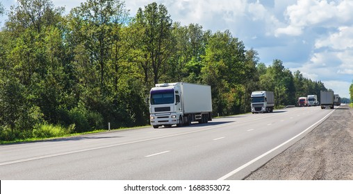 Trucks deliver cargo in opposite directions on a suburban highway on a summer day.
