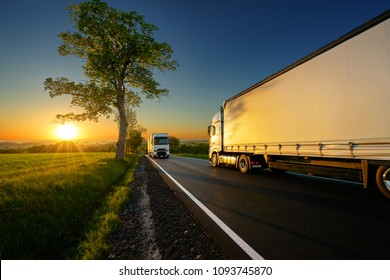 Trucks driving on the asphalt road between trees in a rural landscape at sunset