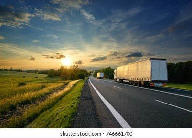 Trucks driving towards the setting sun on the road in rural countryside