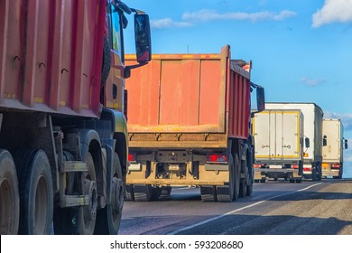 trucks and dump trucks go on highway in sunny day
