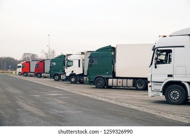 Trucks parked in a long row. Parking by the highway.
