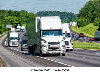 Trucks and personal vehicles navigate a busy interstate. Image shot on hot day. Heat waves from asphalt create distortion, especially on vehicles farther from camera, enhancing long telephoto effect.