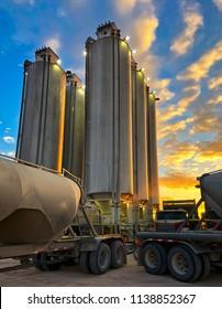 Trucks pumping sand into silos.