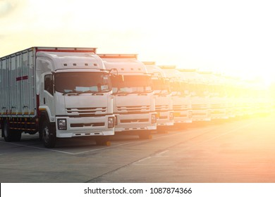 Trucks in a row with Container background on the road with sunrise. Logistic and Transport concept.