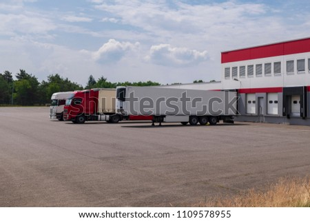 Trucks and trailers at the loading ramp of a warehouse