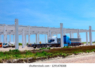 Trucks with trailers are transporting long and heavy concrete beams to construction site for industrial edifice.