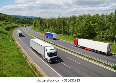 Trucks traveling on an asphalt highway between forests. Wooded mountains in the background. View from above. Sunny summer day.