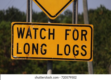 TRUCKS TURNING WATCH FOR LONG LOGS SIGN
