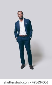 True elegance. Full length of handsome young African man in smart casual jacket holding hands in pockets and looking at camera while standing against grey background