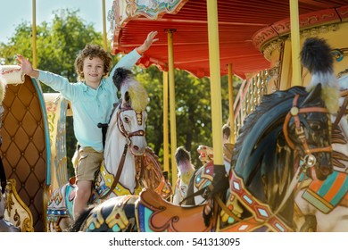 True emotion of happiness on the face of a young boy with rised hands sitting on the horse at the carousel. Nice summer weather with a lot of sunshine.