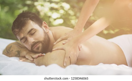 True enjoyment and relaxation. Young men enjoy in massage by his girlfriend.  Close up image.