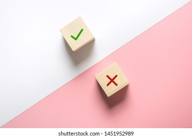True and false symbols accept rejected for evaluation, Yes or No on wood blogs on pink and white background.