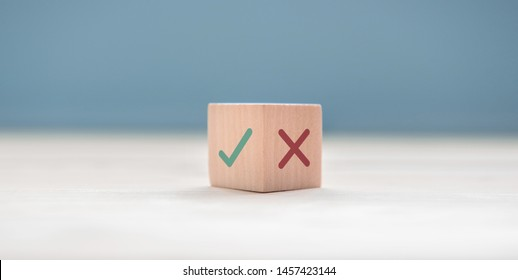 True and false symbols accept rejected for evaluation, Yes or No on wood blogs on blue background.