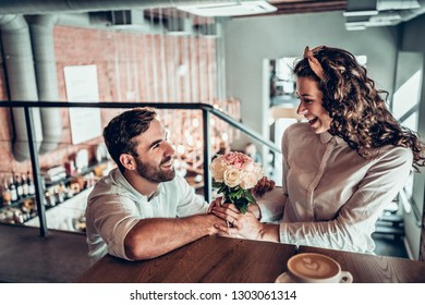True feelings. Beautiful romantic couple in cafe. Man is presenting flowers to his wife.