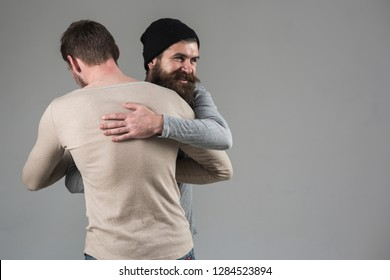 True friendship. Happy men in friendly relations. Best friends greeting each other. Bearded man shaking hands and hugging male friend. Bonds of friendship. Meeting of old friends.