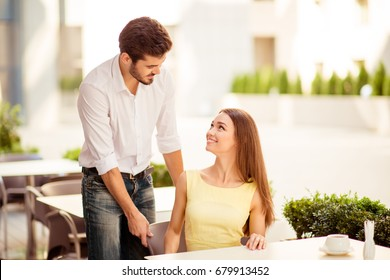True gentleman! Young handsome brunet lover is adjusting the chair of his happy lady, both well dressed, at a sunny terrace of restaurant
