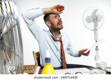 The true hell is here. Young man suffering from the heat in the office. Fans do not help, it's like sahara in the centre of the city. Concept of office worker's troubles, business, problems and stress