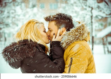 true love. Man and woman happily kissing on the street in the snow. Horizontal color photo