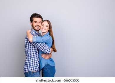 True love, trust, friendship, happiness. Two young cute lovers are looking at the camera and smile, wearing casual outfits, hugging gently on the pure background near copy space