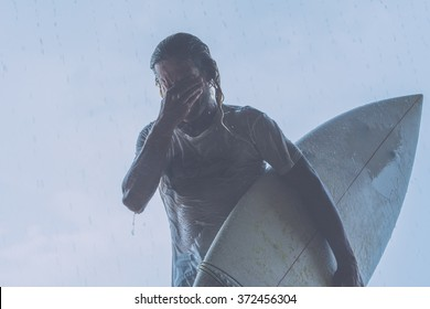 true surfer with surf board in the rain