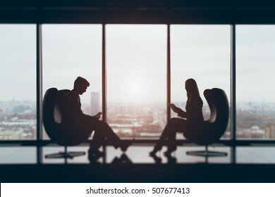 True tilt shift shooting of silhouettes of businessman and businesswoman sitting in front of each other with their gadgets in contemporary office interior, blurred view from top of city in background