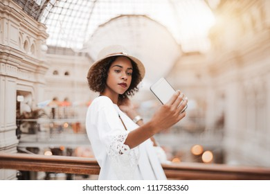 True tilt-shift shot with selective focus: cute young black tourist female in the hat is taking the selfie on her smartphone indoors of a huge shopping mall; selective focus on hand and face