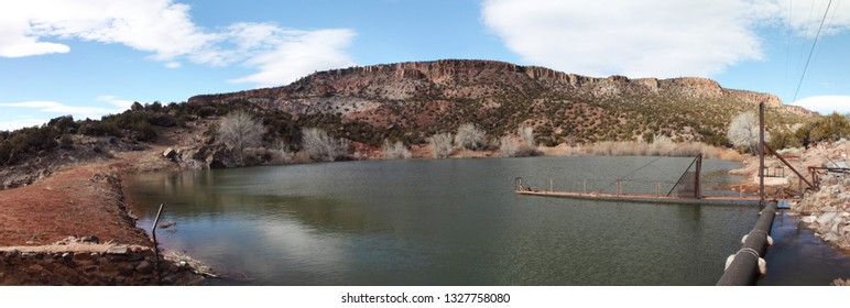 True wide panorama of a calm irrigation reservoir in the mountains of New Mexico in the early spring