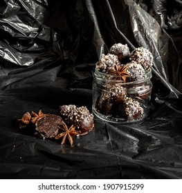 Truffles are organic with only useful ingredients, sprinkled with air amaranth.  on a black background in a transparent transparent jar of chocolate candies. Flat lay
