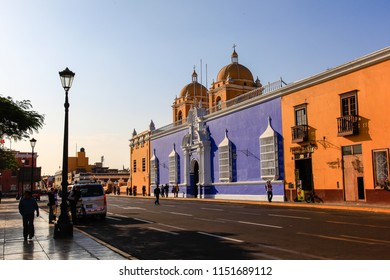 Trujillo, Peru, July 2018: Colored buildings next to the cathedral, in the city's main square, bathed in the light of sunset