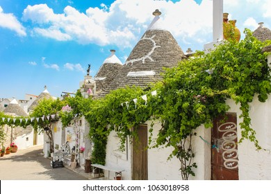 Trulli of Alberobello (Bari): typical houses built with dry stone walls and conical roofs. Blue cloudy sky. Puglia, Italy