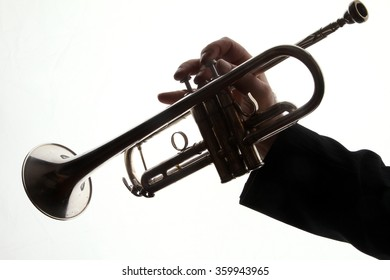 trumpet and player - young man playing a trumpet - back light - shadows - musical instruments - valves and tubes - mouthpiece for playing