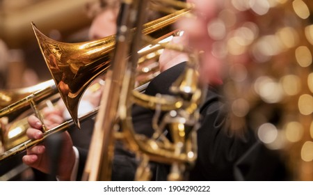 Trumpet professional player with symphony orchestra performing in concert on background.