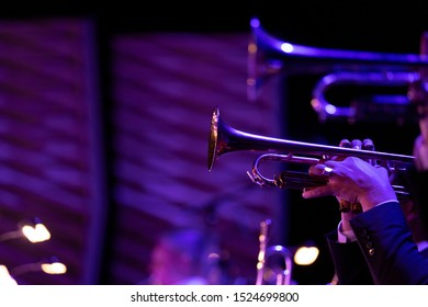 Trumpet section of a big band playing during a concert in purple stage lights
