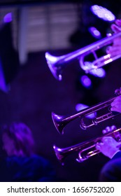 The trumpet section of a big band is playing a chorus during a concert on stage in purple stage lights
