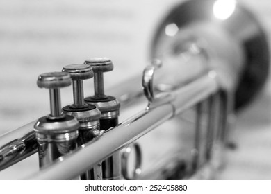 Trumpet as seen from behind with blurred out sheet music as background and first keys in focus, black and white.