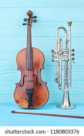 Trumpet and violin on colored background. Vintage trumpet, violin and fiddle stick. Objects of classical music.