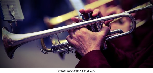 trumpeter plays his trumpet in the brass band during live concert
