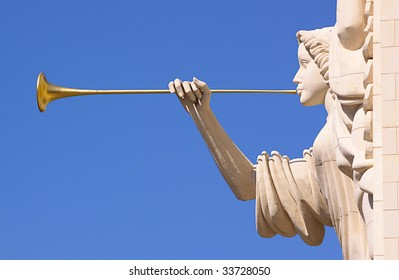 A trumpeting golden music angel statue detail over blue sky.