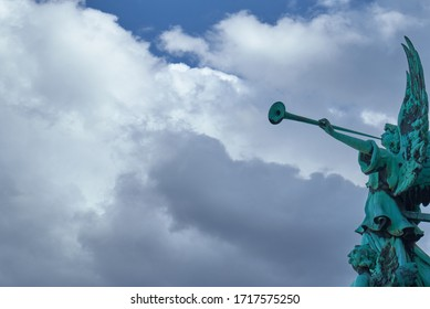 Trumpeting old bronze angel statue covered with green verdigris playing a celestial fanfare against a sunny sky with dramatic clouds.