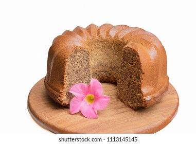 truncated bundt cake with millet flour, walnuts and poppy seed. decorated with a mandevilla blossom. white background.
