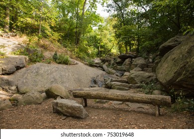 A trunk bench in New York City Central Park. It is in The Ramble. A small waterfall flows through the stones and rocks. The picture was taken in October 2017.