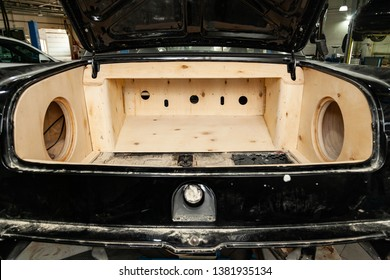 Trunk of a black car sedan with a box made of wood and sawn holes for the installation of subwoofers and speakers for an audio system with a loud sound and bass. Auto service industry and tuning.