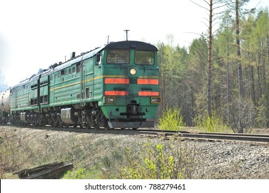 Trunk two-section locomotive, going by rail with freight cars. A train. Railway. Russia.